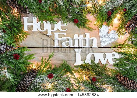 Christmas tree garland border with snow, lights, tin heart and the words Hope, Faith, Love on antique rustic wooden background