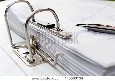 Pen on file folder with documents storage of contracts. selective focus.