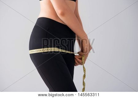 My diet. Cropped picture of young woman measuring her figure with centimeter while standing on isolated grey background