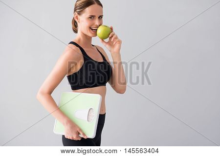 Only apples. Cropped image of cheerful and smiling young woman eating green apple and holding scales while standing on isolated grey background