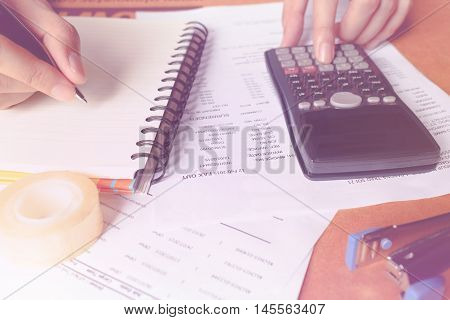 savings finances economy and home concept - close up of man holding pen with calculator stapler tape counting making notes at home or office soft focus.