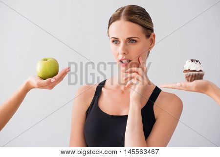 My choice. Wistful young woman choosing what to eat apple or cake while standing on isolated grey background