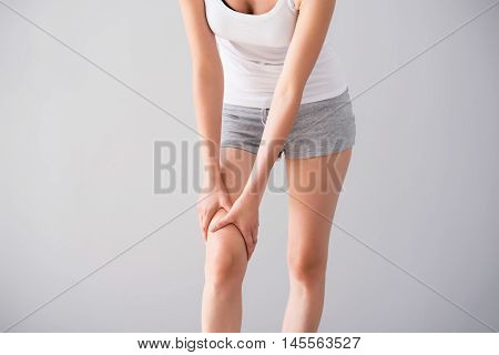 Traumatic sport. Cropped image of young woman having legs ache being on isolated grey background