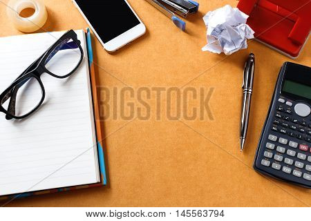 Wood office or home desk table with a lot of things on it. Top view.Notebook pen eye glasses tape phone stapler calculator crumpled paper puncher. can be put some texts or images.View from above with copy space soft focus.