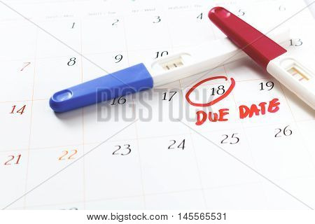 Pregnancy test with positive result lying on calendar background. soft focus.