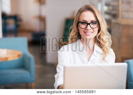 Diligent worker. Happy and smiling young woman using laptop while working and sitting at the table