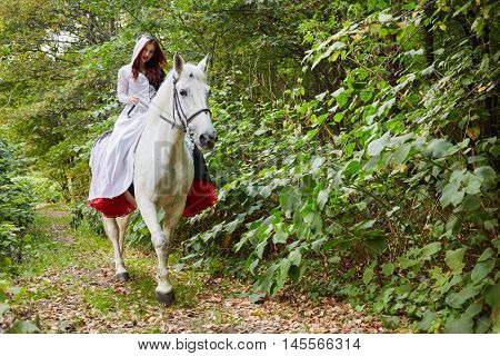 Young woman in black and white dress rides on horseback in park.