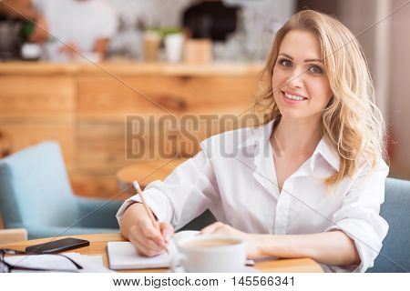 During working day. Portrait of delighted and merry young woman writing something down in her copybook while sitting at table and smiling at camera