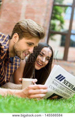 Carefree young man and woman are interested in news. They are looking at paper and smiling. Couple is lying on grass. Guy is drinking coffee