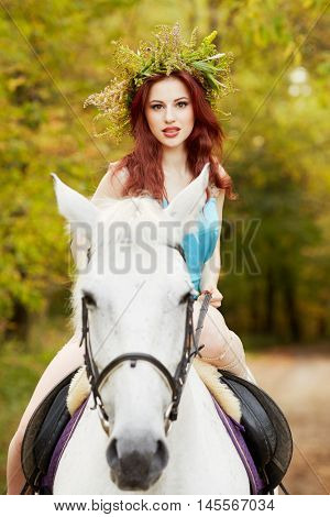 Red-haired woman with floral wreath on head rides on white horse in park.