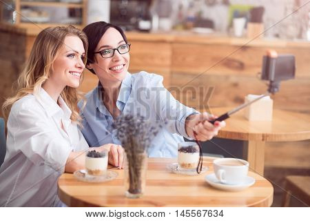 Girls day. Smiling and happy friends making selfie photo using selfie stick and smart phone