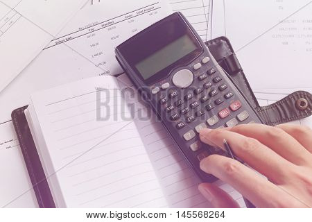 savings finances economy and office concept. Business people counting on calculator notebook holding pen in hand sitting at the table. Close up of hands and stationery soft focus