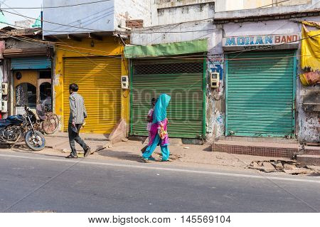 AGRA INDIA - 25TH MARCH 2016: Buildings and streets in Agra India during the day. People and the outside of buildings can be seen.