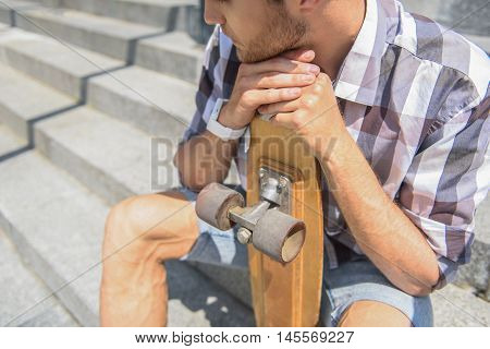 Pensive male skateboarder is sitting on steps. He is leaning head on skate thoughtfully