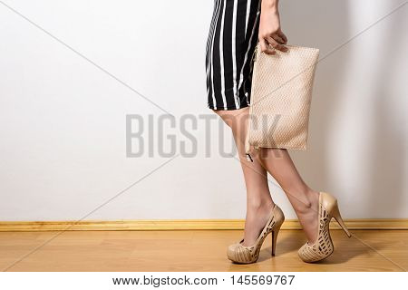 Slim girl in a dress in black and white stripes beige high-heeled shoes is holding a clutch bag