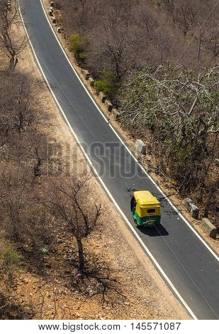 Jaipur India - 22ND MARCH 2016: A high view of a single Tuk Tuk Rickshaw on a rural road in India during the day.