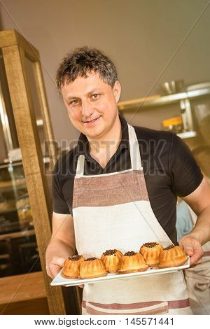 baker concept. Happy baker showing plate of fresh bread in the kitchen of the bakery