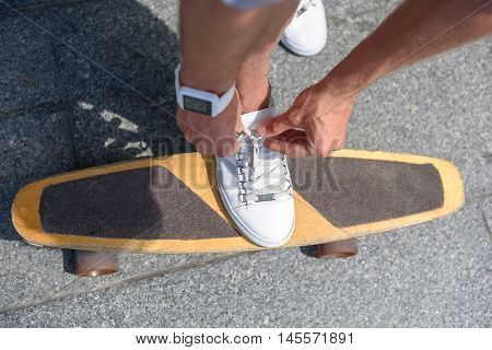 Close up of young skateboarder tying shoelaces on his sneakers. He is wearing tracker