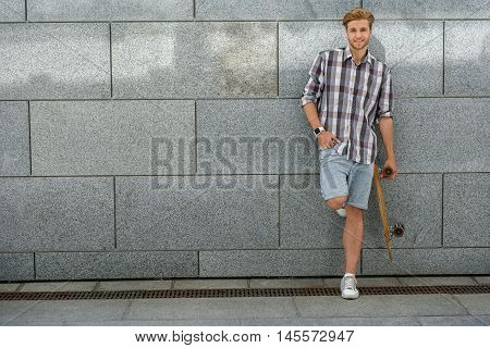 Joyful young man is standing and carrying skateboard. He is leaning on wall with relaxation. Guy is looking at camera and laughing