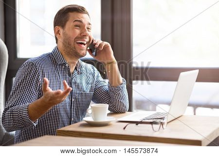 What a good news. Overjoyed content man smiling and sitting at the table while talking on cell phone