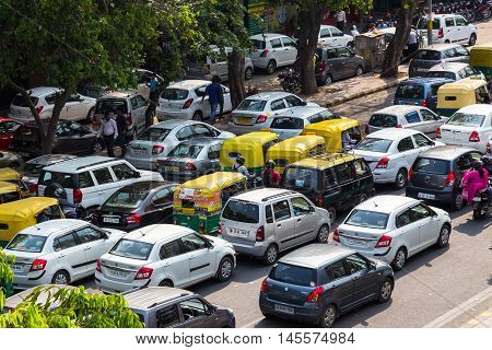 DELHI INDIA - 19TH MARCH 2016: Traffic jams in central India during the day. Tuk Tuk Rickshaws motorbikes cars and people can be seen.