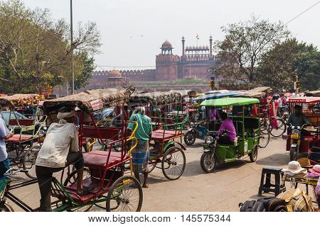 DELHI INDIA - 19TH MARCH 2016: Large amounts of Tuk Tuk Rickshaws in central Delhi during the day. The Red Fort can be seen in the distance.