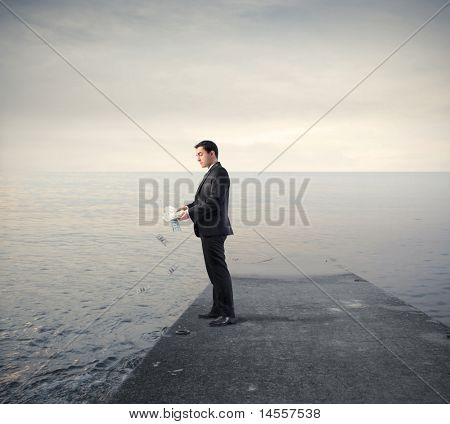 Businessman throwing some banknotes in the sea