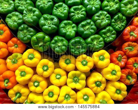 Green yellow and red bell peppers stacked at the market
