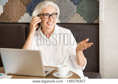 Pleasant talk. Cheerful content senior woman sitting at the table and resting in the cafe while talking on cell phone