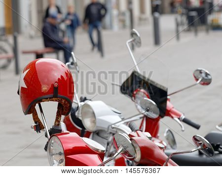 STOCKHOLM SWEDEN - SEPTEMBER 03 2016: Red shining retro helmet on the handlebar of a vespa scooter before the start of the Mods vs Rockers event at the Saint Eriks bridge Stockholm Sweden September 03 2016