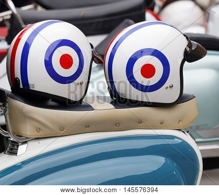 STOCKHOLM SWEDEN - SEPTEMBER 03 2016: Two retro helmets on the saddle of a vespa scooter before the start of the Mods vs Rockers event at the Saint Eriks bridge Stockholm Sweden September 03 2016