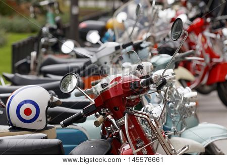 STOCKHOLM SWEDEN - SEPTEMBER 03 2016: Many retro vespa scooters only one scooter and a helmet in focus before the start of the Mods vs Rockers event at the Saint Eriks bridge Stockholm Sweden September 03 2016