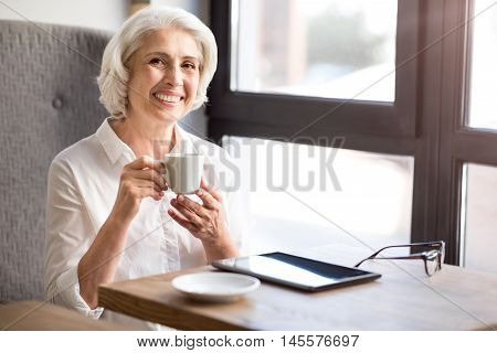 Like my work. Positive delighted beautiful woman sitting at the table and working with papers while expressing gladness