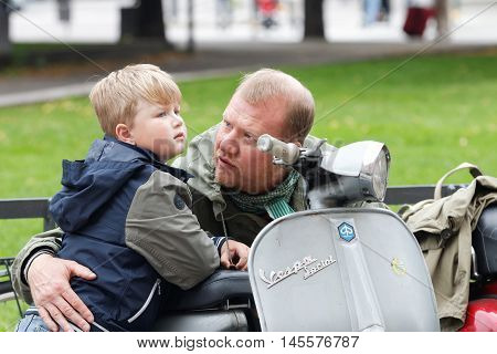 STOCKHOLM SWEDEN - SEPTEMBER 03 2016: Father dressed as mods showing his scooter to his son before the start of the Mods vs Rockers event at the Saint Eriks bridge Stockholm Sweden September 03 2016