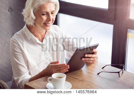 Modern way of communication. Positive delighted sitting at the table and using tablet while expressing gladness