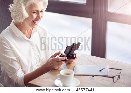 Pleasant time spending. Cheerful delighted senior woman sitting at the table and holding game console while playing video games