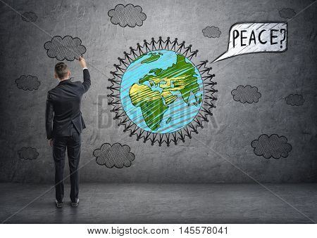 Back view of a businessman drawing clouds and planet Earth with little men around it and thought balloon with 'peace' word on concrete wall. Global communication. International relations.