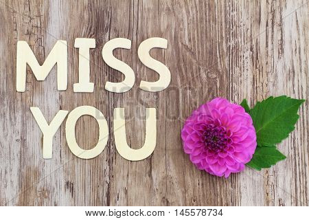 Miss you written with wooden letters and pink dahlia flower