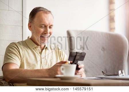 Lets lay. Positive delighted senior man holding game console and playing while sitting at the table