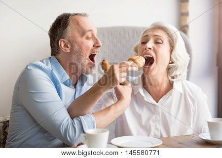 Unforgettable taste. Positive senior loving couple sitting at the table and eating croissants while resting together in the cafe