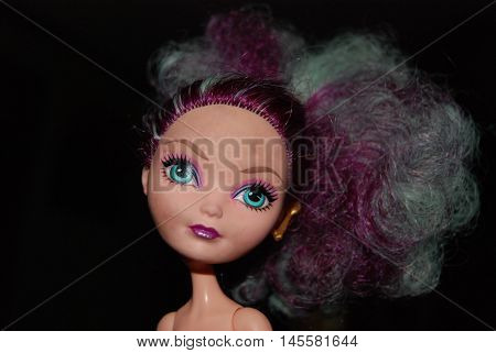 A well loved fashion doll with wild colored hair.