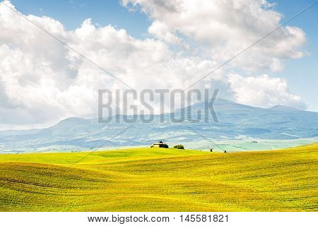 Beautiful tuscan landscape view on the green meadow with farmland house in Italy