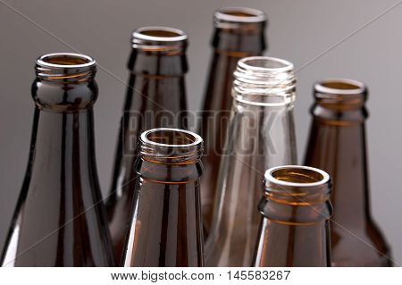 Concept image of glass bottles. A close up of several brown glass bottles and one clear glass bottle.