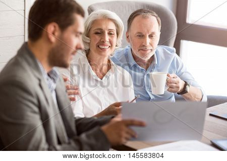 Ready for new bargain. Cheerful senior couple sitting at the table and listening to professional sales manager while expressing positivity