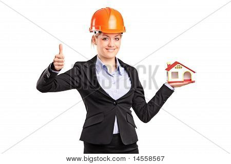Smiling Forewoman Holding A Model House And Giving Thumb Up