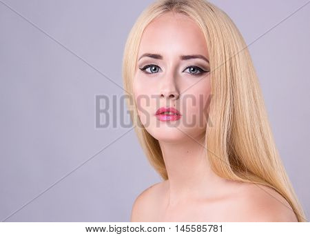 Beautiful blonde model woman face with blue eyes and perfect make-up. Portrait of beauty young blond girl with pink lips. Female face with clear skin close-up. Skincare