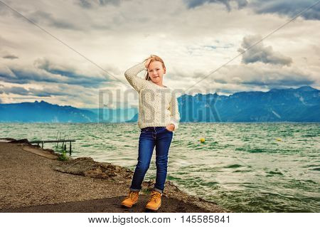 Cute little girl of 8 years old playing by the lake on a very windy day, wearing warm white knitted pullover, arms wide open, toned image