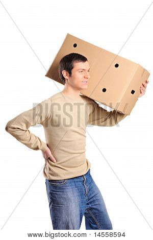 A Young Man Suffering From Back Pain While Lifting A Box