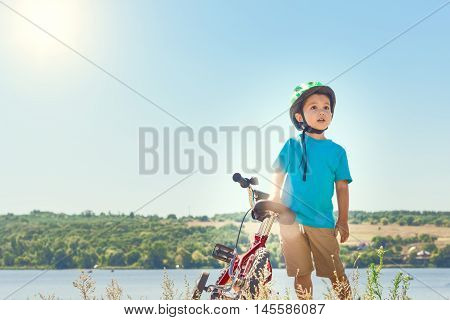 Kid helmet bicycle . Sun shines brightly. Child riding a bicycle. Child with a bicycle on the river bank. Beautiful baby. Toned image.