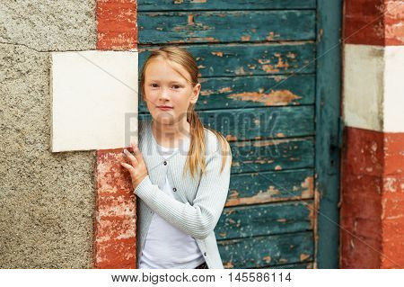 Outdoor portrait of a cute little girl of 8-9 years old, wearing grey  knitted jacket, standing next to old green door